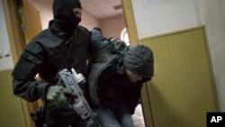 러시아 경찰이 8일, 넴초프 전 부총리 살해 용의자 가운데 한 사람으로 추정되는 남성을 끌고 가고 있다.