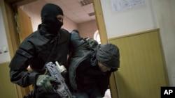 ຕຳຫຼວດນຳໂຕຊາຍຄົນນຶ່ງ ທີ່ສົງໄສວ່າ ເປັນຜູ້ຄາດຕະກຳ ທ່ານ Boris Nemtsov ໄປຂຶ້ນສານ ທີ່ມົສກູ, ວັນທີ 8 ມີນາ 2015.
