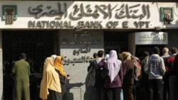 People in Cairo wait to withdraw money from the bank. The exchange rate of Egypt's money has dropped to its lowest level in 6 years