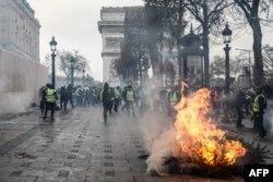ພວກປະທ້ວງ ທີ່ພາກັນໃສ່ເສື້ອກັກກັນໜາວສີເຫຼືອງ ທີ່ພາກັນຢືນຢູ່ ຂ້າງໆຕົ້ນໄມ້ທີ່ກຳລັງໄໝ້ຢູ່ ໃນຂະນະທີ່ພວກເຂົາເຈົ້າພາກັນທຳການປະທ້ວງ ຄ່າຄອງຊີບທີ່ຖີບຕົວສູງຂຶ້ນນັ້ນທີ່ພສກເຂົາເຈົ້າຖີ້ມໂທດໃສ່ການເກັບພາສີທີ່ໜັກໜ່ວງນັ້ນ ທີ່ປະຕູໄຊ Arc de Triomphe ທີ່ຖະໜົນຫຼັກ Champs-Elysees ໃນປາຣີ, ຝຣັ່ງ, 8 ທັນວາ 2018.