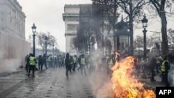 Waandamanaji walova koti manjano wasimama karibu na mti unaowaka moto karibu na mnara Arc de Triomphe mtaa wa Champs-Elysees