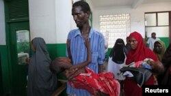 Internally displaced man carries cholera-stricken son through pediatric ward, Banadir hospital, Mogadishu, Aug. 25, 2011.