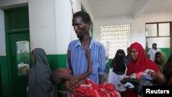 Un déplacé portant son enfant victime du choléra