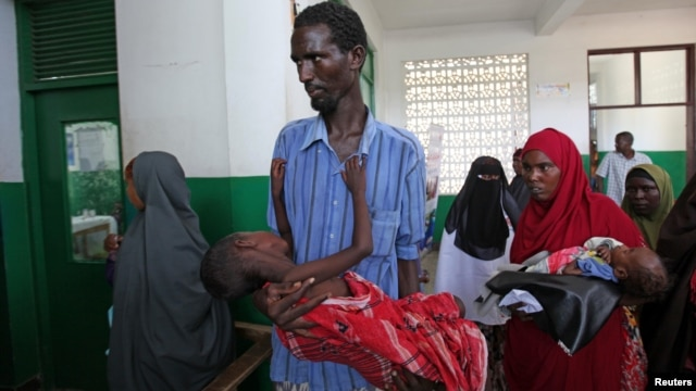 Internally displaced man carries cholera-stricken son through pediatric ward, Banadir hospital, Mogadishu, Aug. 25, 2011.