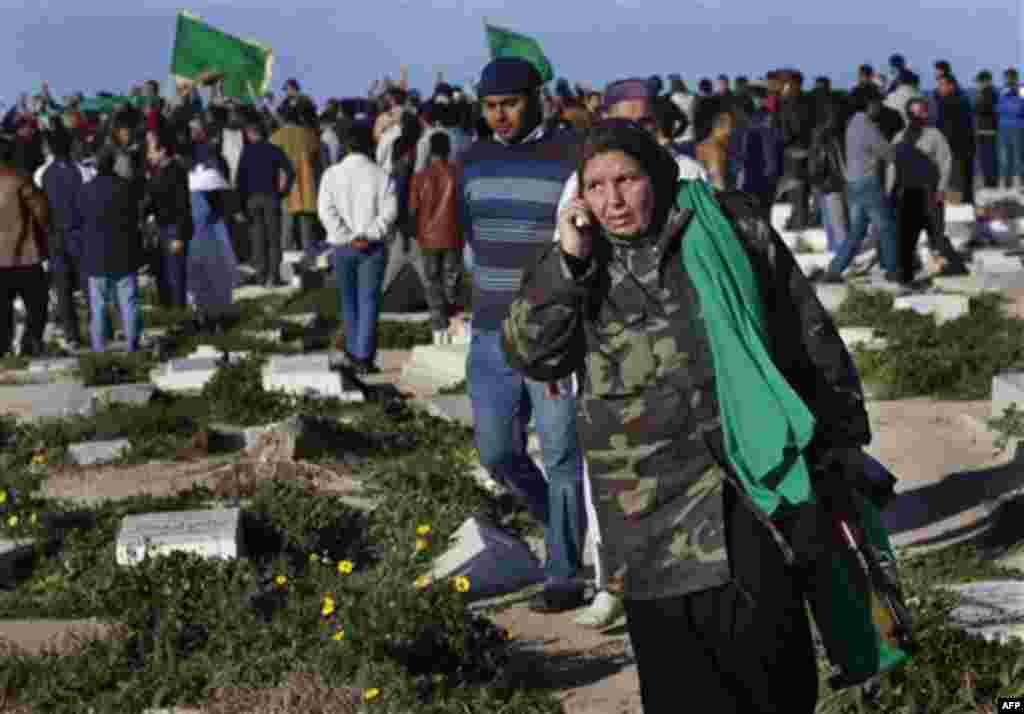 In this image taken during an organized trip by the Libyan authorities, a Libyan woman holding an automatic rifle speaks on the phone as men gather around the grave of a man being buried in Tripoli, Sunday March 20, 2011. The cause of death was unknown.