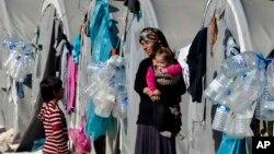 지난달 19일 시리아와 터키 국경지역인 수루크 난민캠프에서 쿠르드족 여성이 아이를 안고 있다. (자료사진)