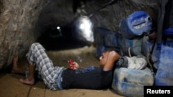 A Palestinian tunnel worker uses his mobile as he rests inside a smuggling tunnel beneath the Gaza-Egypt border in the southern Gaza Strip, July 19, 2013.
