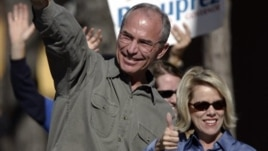 Bob Beauprez and wife Claudia gesture to supporters as they drive by at a honk and wave, Tuesday, Nov. 7, 2006, in Denver.