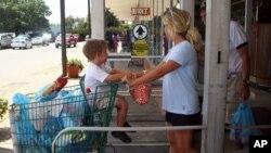 ایک خاتون اپنے بچے کے ساتھ گروسری سٹور سے سودا خرید کر باہر آ رہی ہے۔ فائل فوٹو