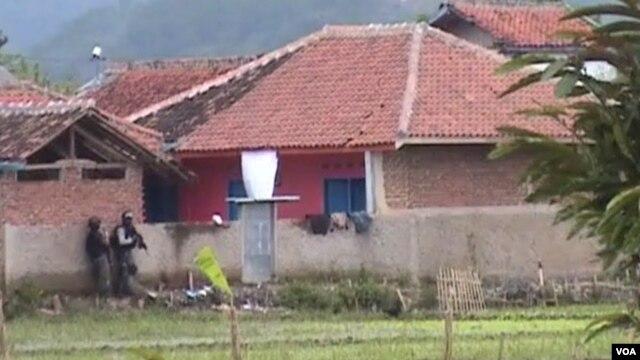Dua petugas Densus 88 sedang mengintai rumah bercat merah (kanan) yang di dalamnya berisi empat tersangka teroris (foto: Wulan/VOA).