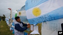 A man ties an Argentine flag carrying solidarity messages to a fence at the Mar de Plata Naval Base after the navy announced a sound detected during the search for the missing ARA San Juan submarine was consistent with that of an explosion, in Mar de Plata, Argentina, Nov. 23, 2017.