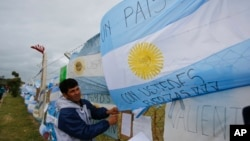 A man ties an Argentine flag carrying solidarity messages to a fence at the Mar de Plata Naval Base after the navy announced a sound detected during the search for the missing ARA San Juan submarine was consistent with that of an explosion, in Mar de Plat
