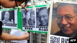 A protester affixes pictures of Chinese writer Mo Yan (L) and Chinese dissident Liu Xiaobo (R) to a gate during a demonstration in front of the Chinese liaison offices demanding the release of Chinese Liu in Hong Kong, October 13, 2012.