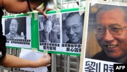 FILE - A protester affixes pictures of Chinese writer Mo Yan (L) and Chinese dissident Liu Xiaobo (R) to a gate during a demonstration in front of the Chinese liaison offices demanding the release of Chinese Liu in Hong Kong.
