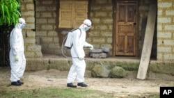 Nhân viên y tế xịt thuốc khử trùng bên ngoài căn nhà của một người bị nghi nhiễm Ebola ờ vùng ngoại ô Freetown, Sierra Leone., ngày 21 tháng 10, 2014.