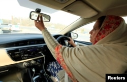 "FILE - Yasmin Perveen, one of the pioneer women ""captains"" of Careem, adjusts her rearview mirror while driving her car in Islamabad, Pakistan, Dec. 7, 2016. In Saudi Arabia, only Saudi men will be allowed to drive Uber or Careem cars."