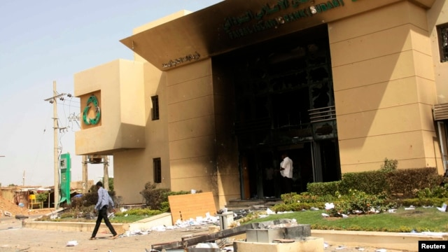 A man passes a bank building burnt during protests over cooking oil and fuel subsidy cuts in Khartoum, Sept. 26, 2013.