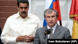 FILE - Venezuela's President Nicolas Maduro, left, listens as CEO of state-controlled Russian oil company Rosneft Igor Sechin speaks during a ceremony for naming a street after late Venezuelan President Hugo Chavez in Moscow, Russia, on Tuesday, July 2, 2013.