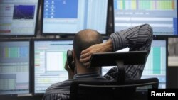 A trader makes a phone call at his desk at the Frankfurt stock exchange, July 24, 2012.