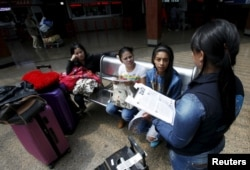 FILE - A Colombian health worker gives travelers information on how to prevent the spread of the Zika virus, at the main bus terminal in Bogota, Colombia, Jan. 31, 2016.