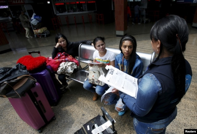 A Colombian health worker gives travellers information on how to prevent the spread of the Zika virus, at the main bus terminal in Bogota, Colombia, Jan. 31, 2016.