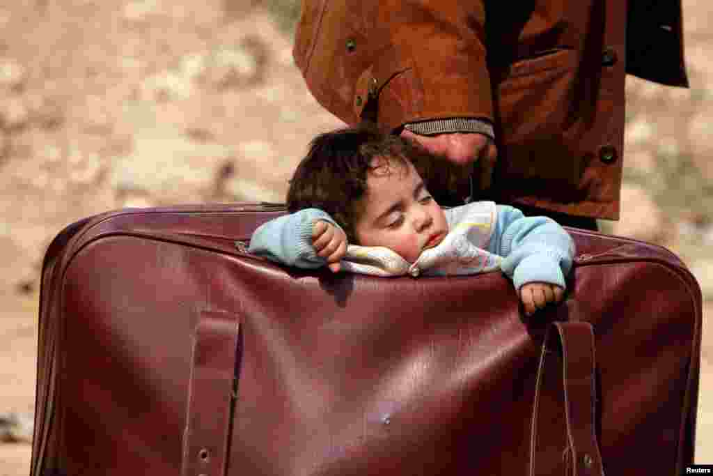 A child sleeps in a bag in the village of Beit Sawa, eastern Ghouta, Syria.