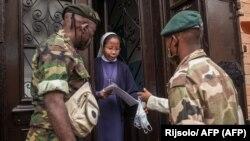 Des soldats de l'armée malgache distribuent des masques et des échantillons d'une tisane présentée par le président Rajoelina comme un remède contre le coronavirus à la population à Antananarivo à Madagascar, le 22 avril 2020.