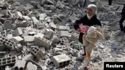 Devojčica nosi svoje stvari preko ruševina posle napada snaga sirijskog predsednika Bašara Al Asada, 14. januar 2014.