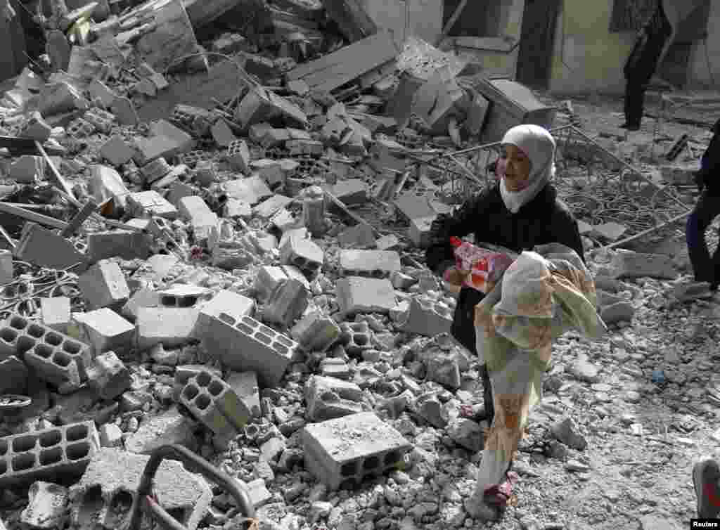 A girl carries her belongings as she walks on rubble at a site hit by what activists said was an airstrike by forces loyal to Syria's President Bashar al-Assad in Arbeen, Jan. 14, 2014.