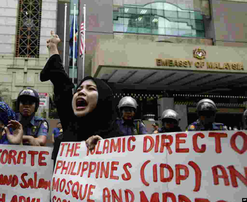 Philippine Muslim protesters shout slogans against the military assault launched by Malaysian forces in Borneo during a rally at the Malaysian Embassy east of Manila, Philippines, March 5, 2013.