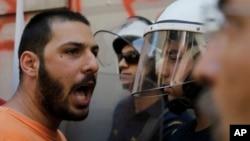 """一名示威者在警察面前高叫""""不""""口號。"""