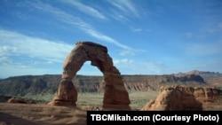 """Mikah Meyer berdiri di bawah """"Delicate Arch"""" di taman nasional Arches di Utah (foto: dok)."""