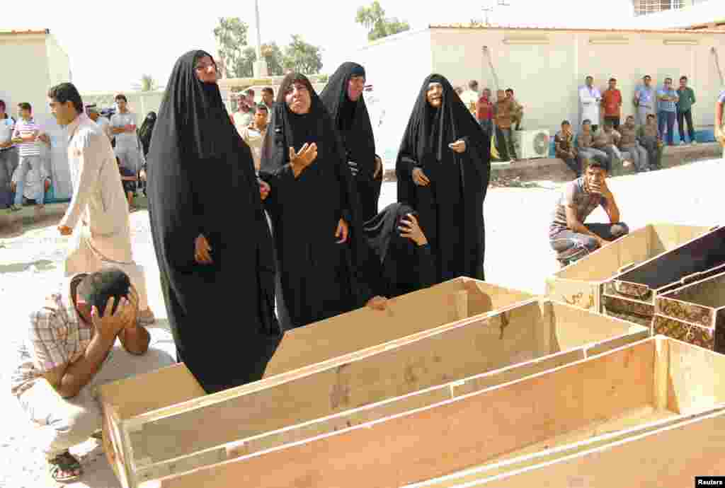 Women react near empty coffins as they wait to claim the bodies of their relatives, who were killed by gunmen, at a hospital morgue outside of Baghdad, Sept. 4, 2013.