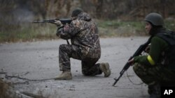 지난 12일 우크라이나 동부 도네츠크 인근 페스키 마을에서 우크라이나 자원 병력이 총을 겨누고 있다.