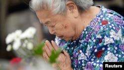 ແມ່ຍິງຍິ່ປຸ່ນຄົນນຶ່ງ ນົບໄຫວ້ເຖິງດວງວິນຍານ ຂອງບັນດາຜູ້ເສຍ ຊີວິດ ທີ່ສວນ ສັນຕິພາບ ທີ່ເປັນອະນຸສອນສະຖານ ຂອງການຖີ້ມ ລະເບີດນິວເຄລຍ ໃສ່່ເມຶອງ Hiroshima ໃນປີ 1945, ວັນທີ 6 ສິງຫາ 2014.
