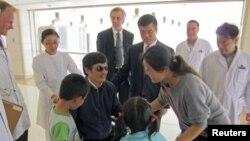 ນັກເຄື່ອນໄຫວຕາບອດຈີນ ທ່ານ Chen Guangcheng (ກາງ) ລົມກັນກັບພັນລະຍາຂອງທ່ານ ນາງ Yuan Weijing ແລະພວກລູກໆ ໃນຂະນະທີ່ເອກອັກຄະລັດຖະທູດສະຫະລັດ ປະຈຳປະເທດຈີນ ທ່ານ Gary Locke ລະຫວ່າງທ່ານ Chen ກັບເມຍ) ຢືນເບິ່ງ ຢູ່ໂຮງໝໍແຫ່ງນຶ່ງ ໃນນະຄອນຫຼວງປັກກິ່ງ (3 ພຶດສະພາ 2012)