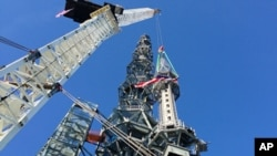 The silver spire topping One World Trade Center in New York is lifted as it is fully installed on the building's roof, bringing the structure to its full, symbolic height of 1,776 feet on May 10, 2013 .