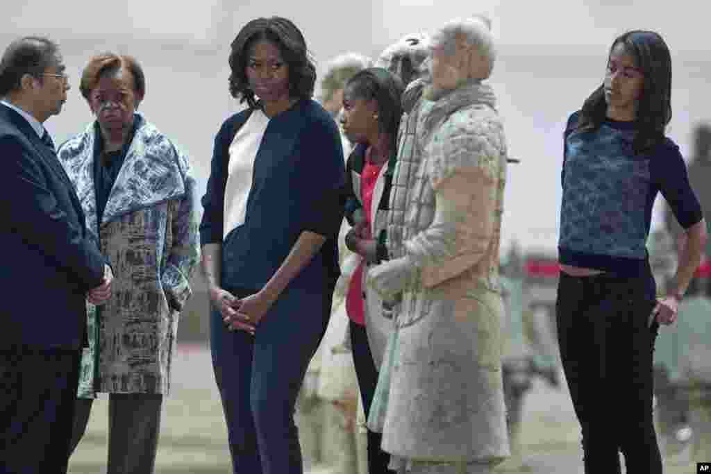 U.S. first lady Michelle Obama looks at a terracotta warrior as she visits Qinshihuang Terracotta Warriors and Horses Museum with her daughters, Malia and Sasha, and her mother, Marian Shields Robinson, in Xi'an, March 24, 2014.
