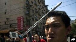 Urumçi'de 2009 yılındaki olaylarda çivili demir sopasıyla Uygur işyerlerine saldıran bir Çinli