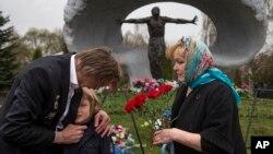 """Alexander Burinin, ancien """"liquidateur"""" de Tchernobyl, son épouse Olga et leur petit-fils Georgy visitant le cimetière de Mitino à Moscou, en Russie, le 26 avril 2016, lors du 30ème anniversaire de l'explosion de la centrale nucléaire de Tchernobyl. Environ 600.000 personnes, souvent appelées """"les liquidateurs"""" de Tchernobyl, ont été envoyées pour combattre l'incendie à la centrale nucléaire après une explosion le 26 avril 1986."""