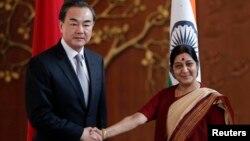 Menlu China Wang Yi (kiri) bertemu Menlu India Sushma Swaraj di New Delhi hari Minggu (8/6).