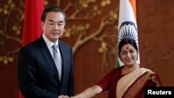 Menteri Luar Negeri China Wang Yi (kiri) berjabat tangan dengan Menteri Luar Negeri India Sushma Swaraj sebum pertemuan di New Delhi 8 Juni 2014.