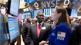 John Evans Atta Mills, the President of Ghana, visits the floor of the New York Stock Exchange, Dec. 15, 2011, and talks with specialist Jennifer Klesaris.