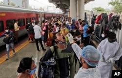 Seorang petugas kesehatan mengambil sampel swab dari seorang pelancong untuk tes COVID-19 di sebuah stasiun kereta api di Mumbai, India, Kamis, 22 Juli 2021. (Foto: AP/Rajanish Kakade)