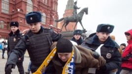 Police officers detain a protester in central Manezhnaya Square in Moscow, on March 2, 2014, during an unsanctioned rally against the Russia's military actions in Crimea.