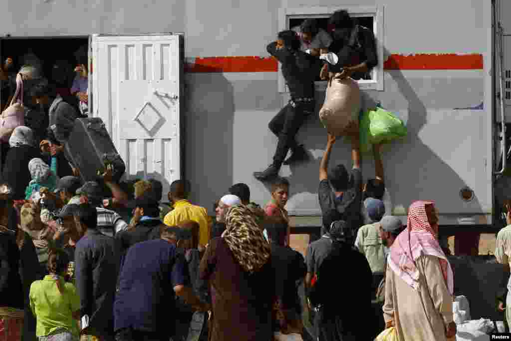 Syria refugees try to enter a truck which will transport them back to their homeland at the Al-Zaatri refugee camp in the Jordanian city of Mafraq, near the border with Syria, July 30, 2013.