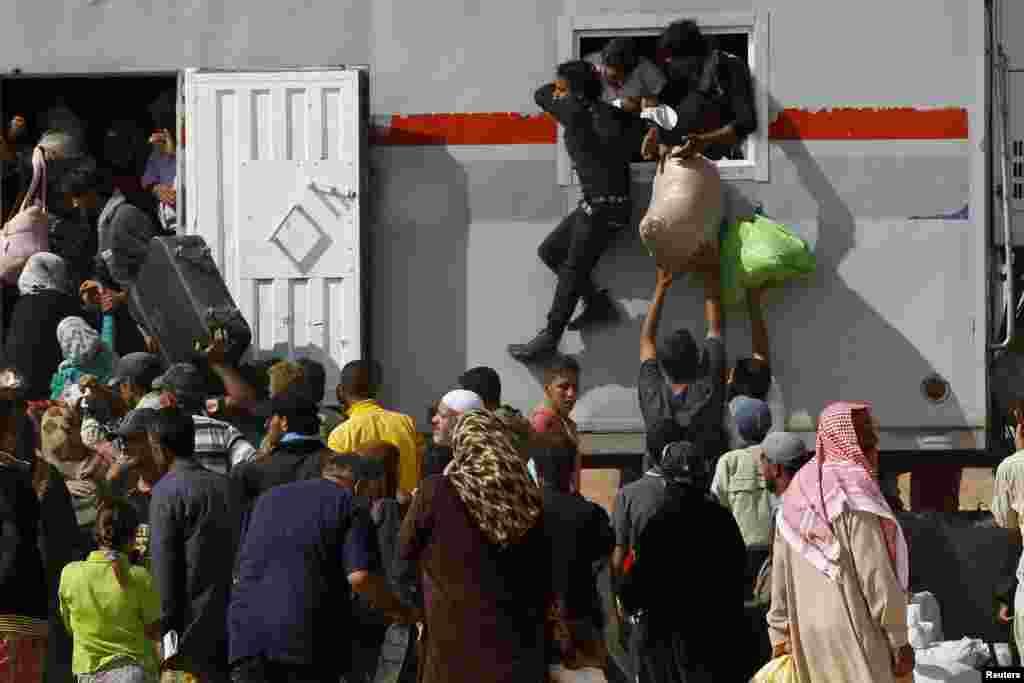 Sirijske izbjeglice prilikom pokušaja da se ukrcaju na jedan od kamiona kojim će se iz kampa u Jordanu vratiti preko granice.