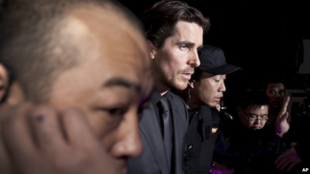 "In this photo taken on Monday, Dec. 12, 2011, actor Christian Bale, center, is led by security guards upon arrival for an event of the Zhang Yimou-directed movie ""The Flowers of War"" in Beijing, China."