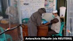 Seorang petugas medis yang mengenakan alat pelindung mengambil sampel darah dari seorang anggota Jamaah Tabligh untuk dites virus corona, Temanggung, Jawa Tengah, 20 April 2020. (Foto: Antara/Anis Efizudin via Reuters)