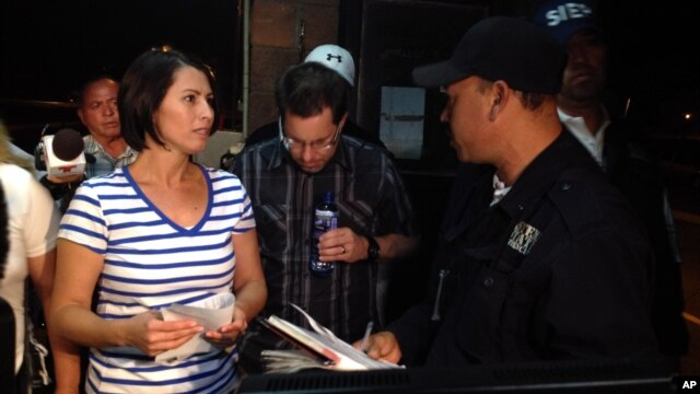 Yanira Maldonado, 42, left, accompanied by her husband, Gary, center, speaks to an official after being released from prison near Nogales, Mexico, May 30, 2013.